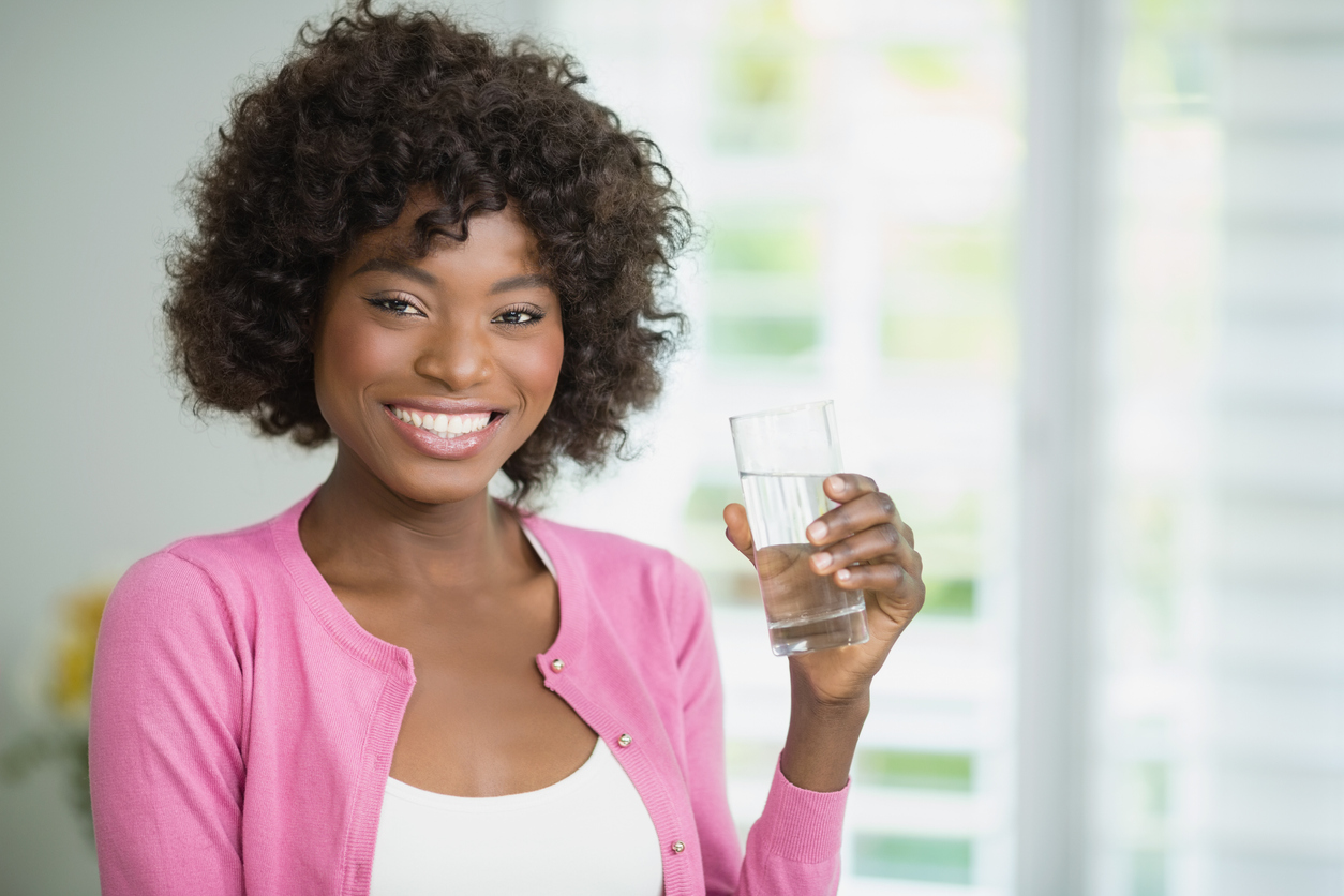 beautiful woman drinking water at home