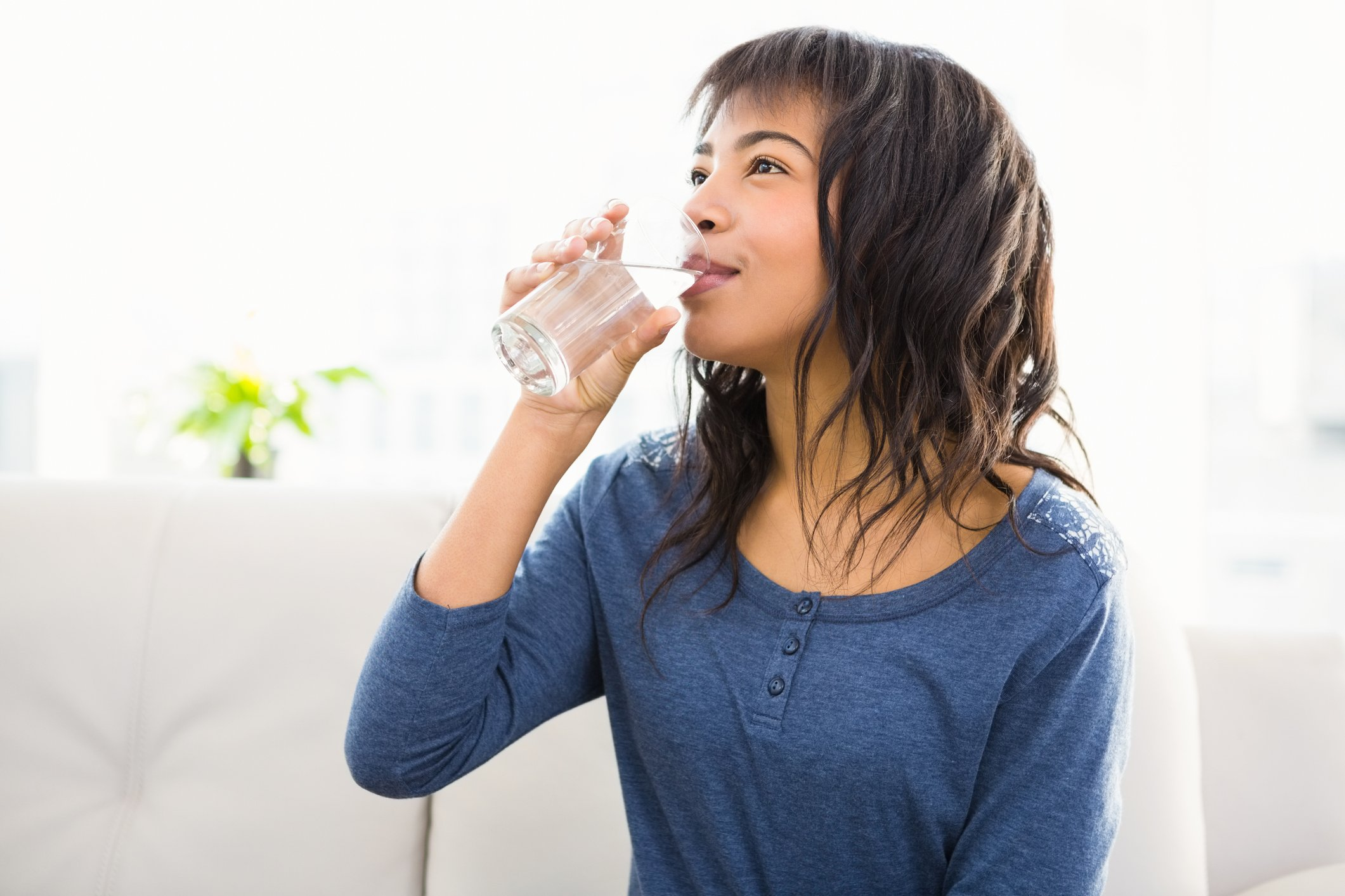 Casual smiling woman drinking some water